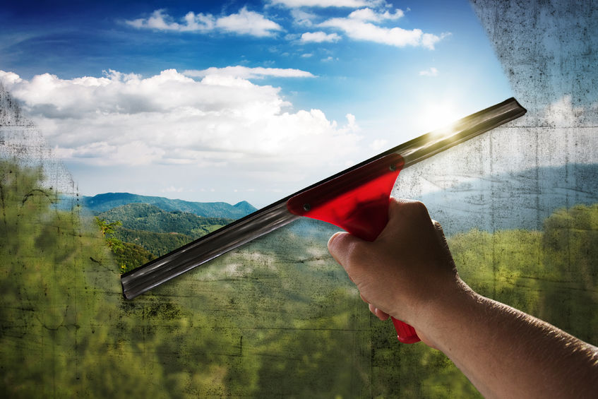 squeegee in use to clean a dirty window